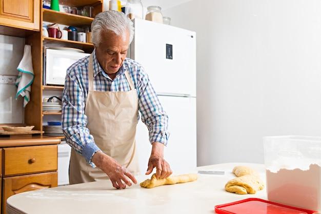 Een oudere man die deeg gebruikt om brood te maken met zijn handen op een tafel, in een keuken, met een schort aan