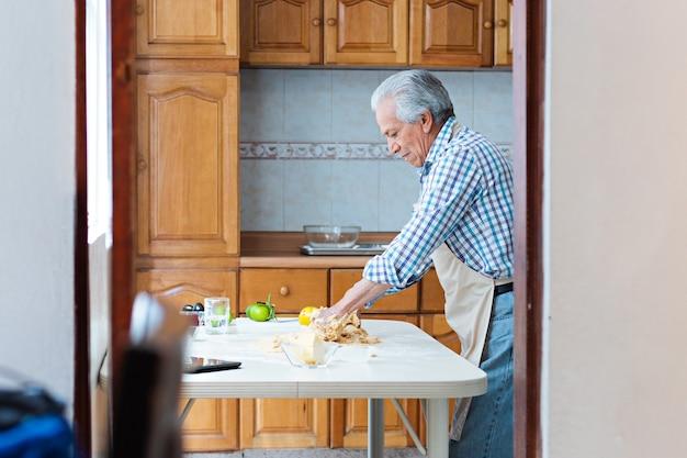 Een oudere man die doug met zijn handen mengt op een tafel, in een keuken, met een schort aan