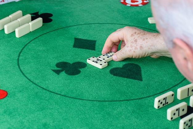 Een oudere man die een dominospel begint.