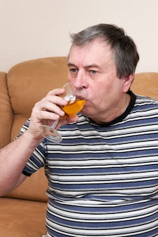 Een oudere man drinkt witte wijn terwijl hij op de bank zit
