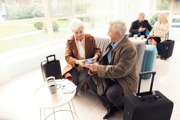 Een oudere man geeft een onverwacht cadeau aan een oudere vrouw.