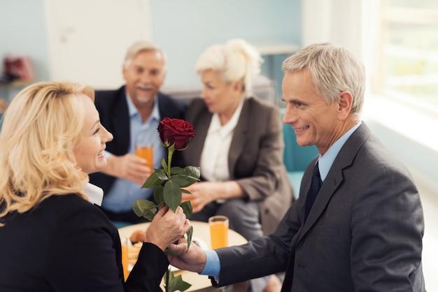 Een oudere man geeft een roos aan een oudere vrouw.