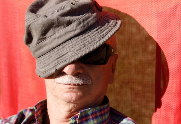 Een oudere man geniet van ontspannen op de zon