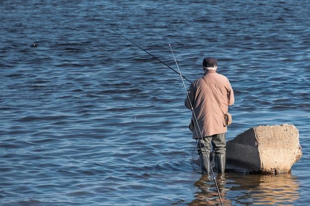 Een oudere man in rubberen laarzen vist met een lijn in het water van een rivier of meer.
