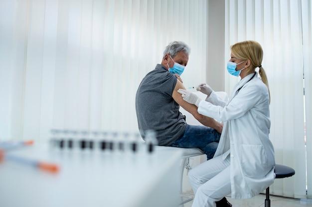Een oudere man krijgt een vaccin neergeschoten door een arts-epidemioloog in het ziekenhuiskantoor tijdens een coronaviruspandemie