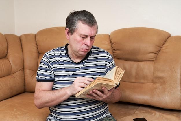 Een oudere man leest een boek terwijl hij op de bank zit