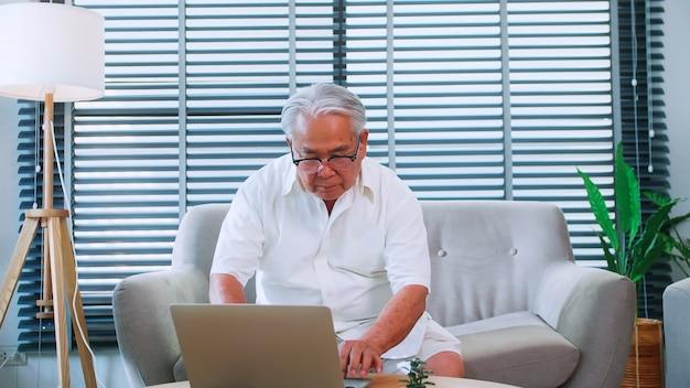 Een oudere man leest nieuws met de tablet op de bank thuis. een oude aziatische man zoekt informatie op internet terwijl hij in de woonkamer zit