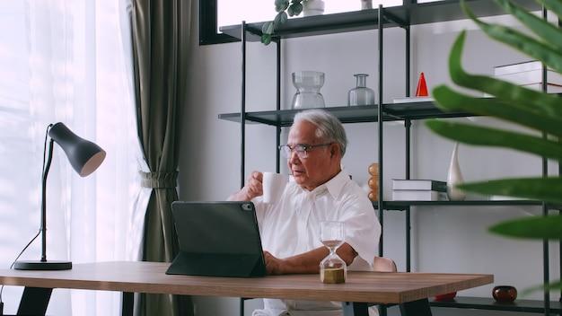 Een oudere man leest nieuws met de tablet op het bureau thuis. een oude aziatische man zoekt informatie op internet terwijl hij aan een tafel zit.
