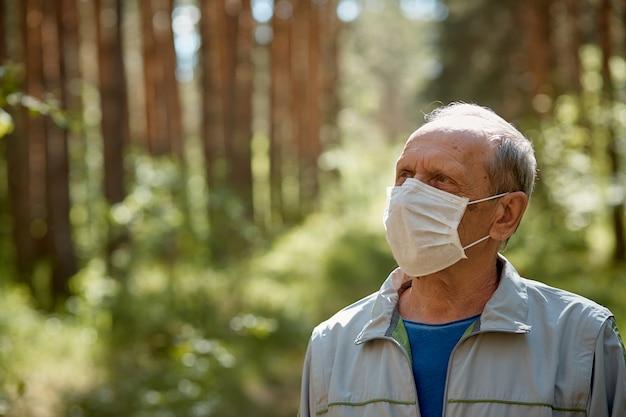 Een oudere man met een beschermend masker loopt in het park, een wandeling in de frisse lucht na quarantaine, een voorzorgsmaatregel tegen het virus