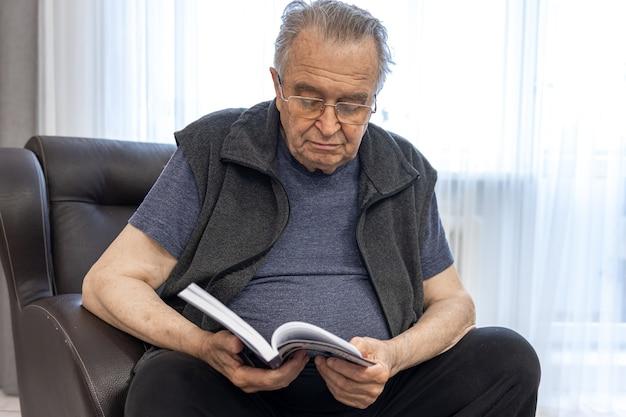 Een oudere man met een bril leest een boek terwijl hij op een fauteuil zit.