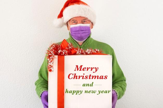 Een oudere man met een kerstmuts met een chirurgisch masker en een kerstcadeaudoos voor thuisbezorging