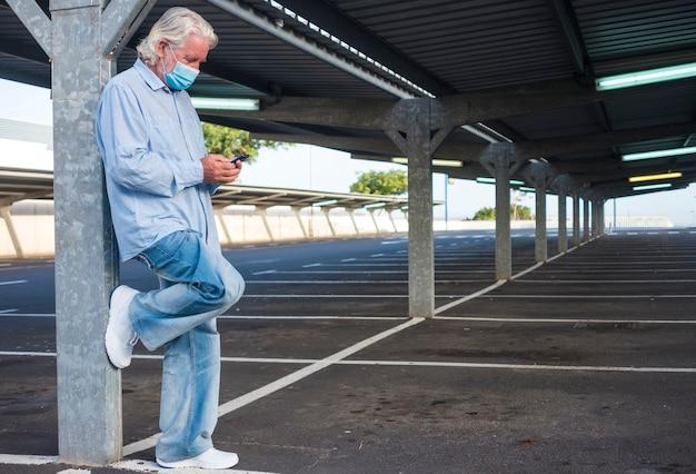Een oudere man met een medisch masker vanwege het coronavirus staat onder de metalen structuur van een verlaten parkeerplaats en kijkt naar zijn smartphone. niemand anders