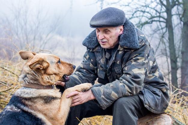 Een oudere man over de natuur communiceert met een hond. een man en een hond zijn vrienden