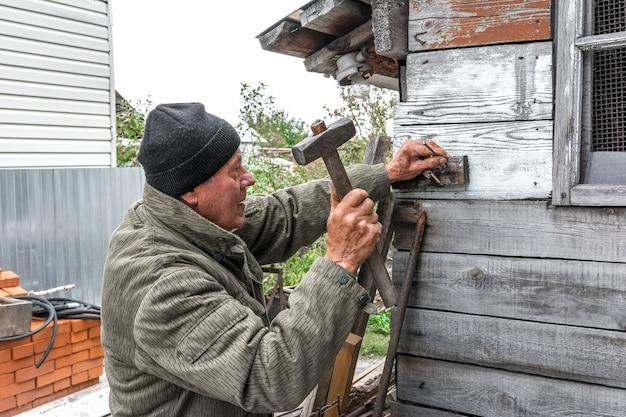 Een oudere man repareert een oude houten schuur hij spijkert de plank aan de muur