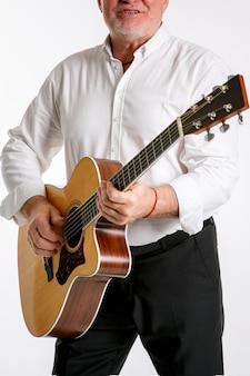 Een oudere man speelt een gitaar geïsoleerd