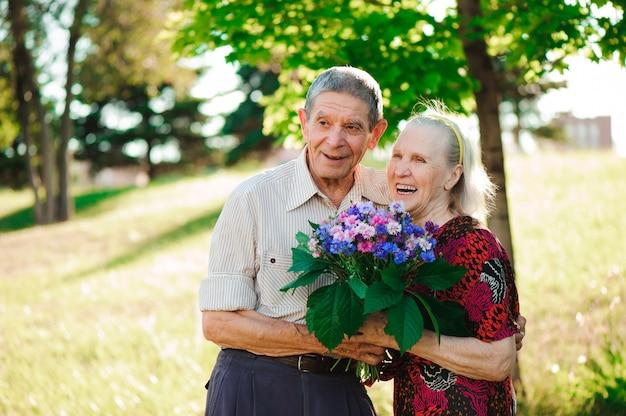 Een oudere man van 80 jaar oud geeft bloemen aan zijn vrouw
