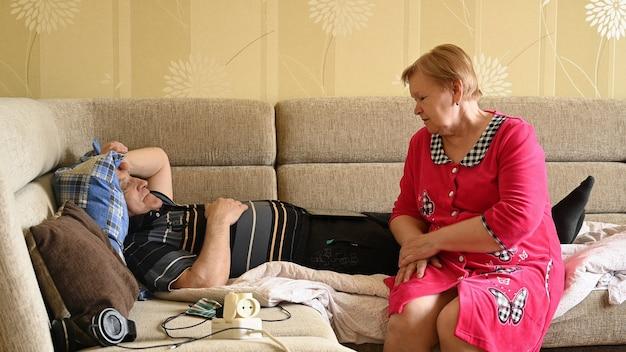 Een oudere man voelt zich niet lekker en zijn vrouw kalmeert hem.