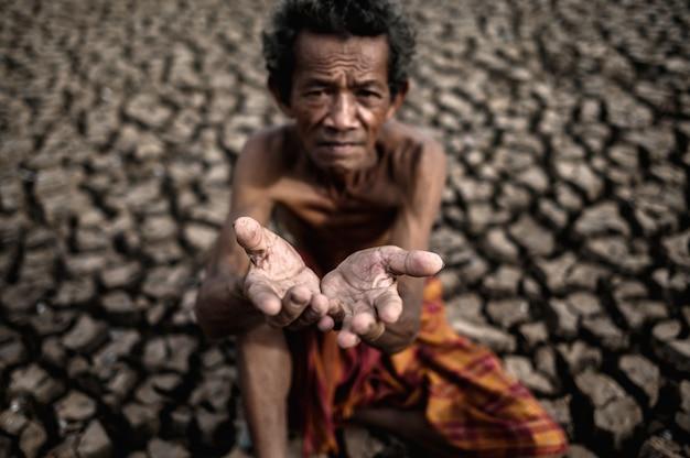Een oudere man zat te vragen om regen in het droge seizoen, de opwarming van de aarde