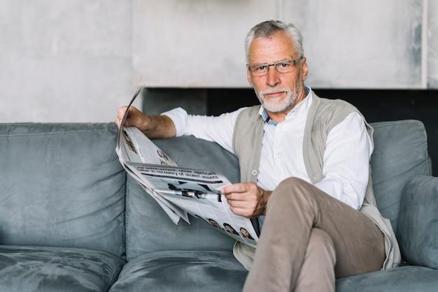 Een oudere man zit op de bank krant lezen