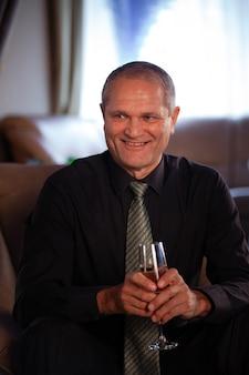 Een oudere mannelijke zakenman in een zwart overhemd glimlacht zittend met een glas wijn in zijn hand