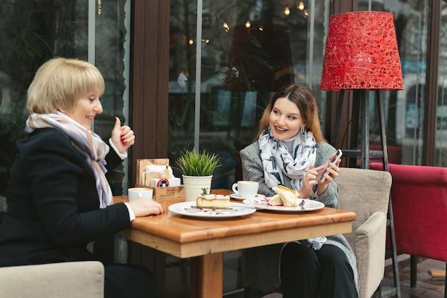 Een oudere moeder en haar volwassen dochter gebruiken een smartphone in een café