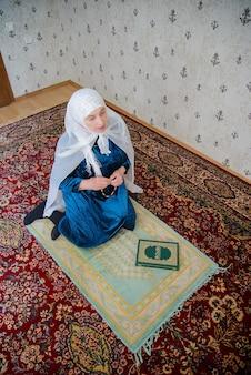 Een oudere moslimvrouw in een witte sjaal en een blauwe jurk die bidt op een gebedskleed in de kamer
