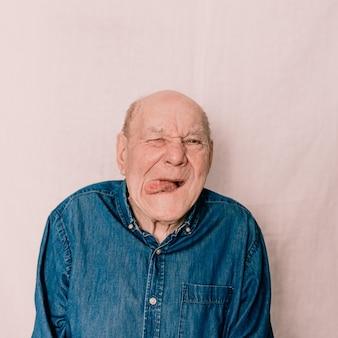 Een oudere oude man trekt een grimas, trekt een gezicht en laat zijn tong zien. gekke grappige man
