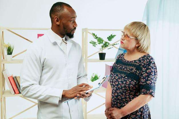 Een oudere vrouw die een therapeut in de kliniek bezoekt voor consultatie en het controleren van haar gezondheid.