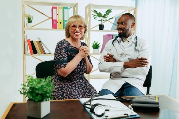 Een oudere vrouw die een therapeut in de kliniek bezoekt voor consultatie en het controleren van haar gezondheid