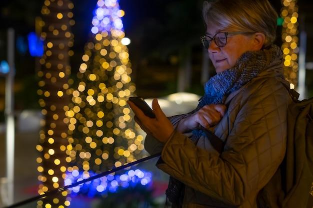 Een oudere vrouw die 's nachts voor een kerstboom staat die is versierd met gele gloeilampen met behulp van de smartphone