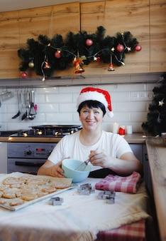 Een oudere vrouw die thuis in de keuken kerstmis behandelt voorbereidt. familie traditie.