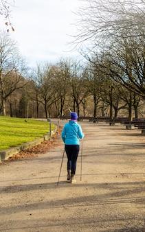 Een oudere vrouw doet aan nordic walking.
