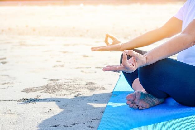 Een oudere vrouw draagt een wit shirt en doet yoga op het zand aan zee