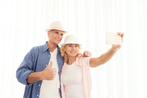 Een oudere vrouw en een oudere man in hoeden selfie maken.