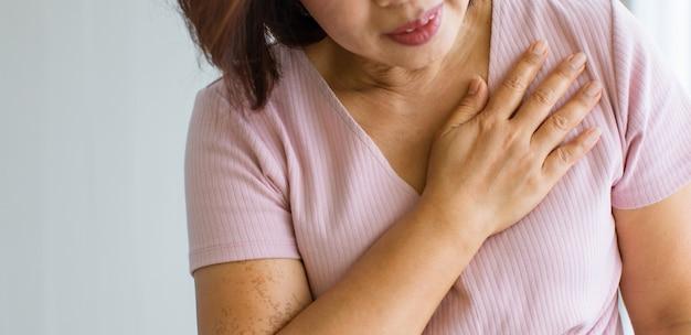 Een oudere vrouw gebruikt de hand op haar borst met pijn en lijdt aan een hartaandoening. concept van st verhoogd myocardinfarct.