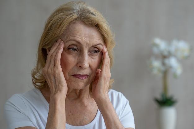 Een oudere vrouw heeft hoofdpijn, ze raakt haar hoofd aan met haar handen en meldt symptomen van duizeligheid
