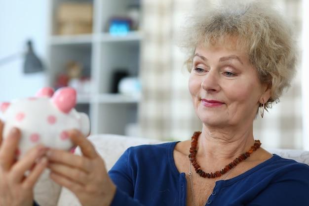 Een oudere vrouw houdt spaarvarken in haar handen en glimlacht