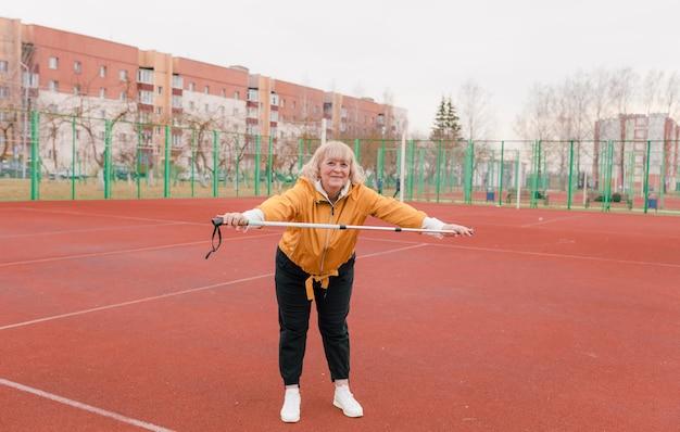 Een oudere vrouw in een geel jasje doet sportoefeningen op een rode loopband. het stadion is een gezonde levensstijl. gepensioneerden en sport. actieve oude vrouw