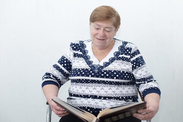 Een oudere vrouw kijkt naar een fotoalbum