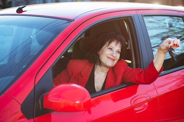 Een oudere vrouw kreeg een rode auto aangeboden. oma houdt sleutels vast en glimlacht