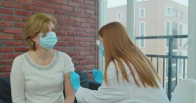 Een oudere vrouw krijgt een vaccin tegen coronavirus, een arts die een masker en handschoenen met een injectiespuit draagt, injecteert een volwassen oudere patiënt.
