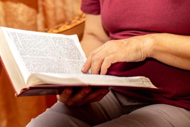 Een oudere vrouw leest de bijbel. bijbel in de handen van een oudere vrouw