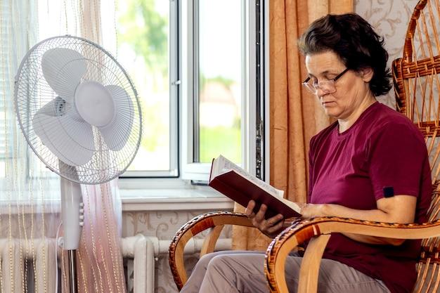 Een oudere vrouw leest de bijbel, zittend in een stoel bij een open raam en een ventilator