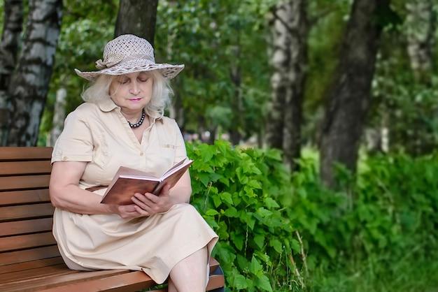 Een oudere vrouw leest een boek in het park