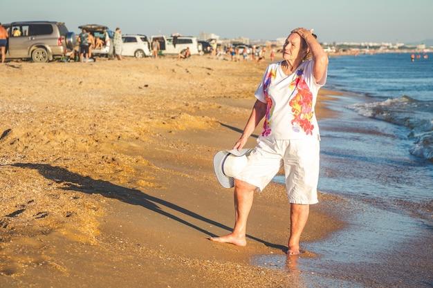 Een oudere vrouw loopt langs de kust. zomervakantie aan zee.