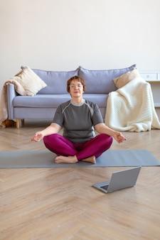 Een oudere vrouw mediteert thuis in een lotushouding voor een laptopmonitor. het concept van een gezonde en actieve levensstijl op oudere leeftijd. verticale foto.