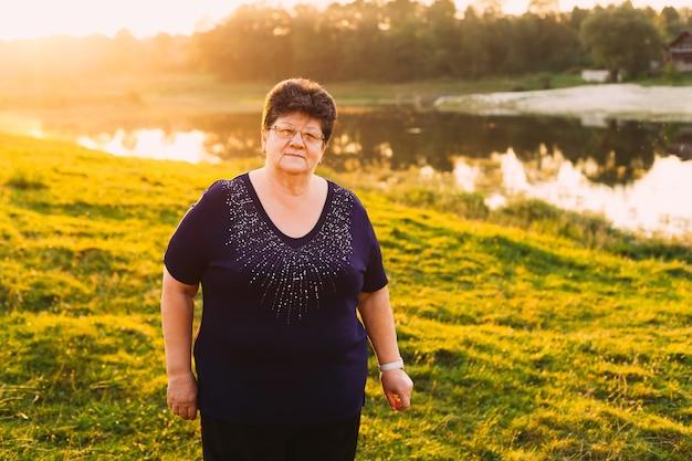 Een oudere vrouw met een bril geniet van een rust aan de oever van een avondmeer
