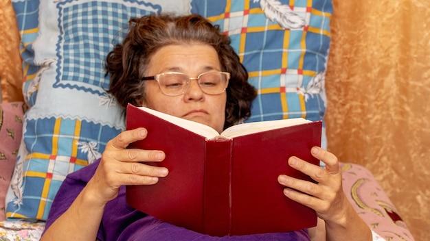 Een oudere vrouw met een bril ligt op de bank en leest een boek