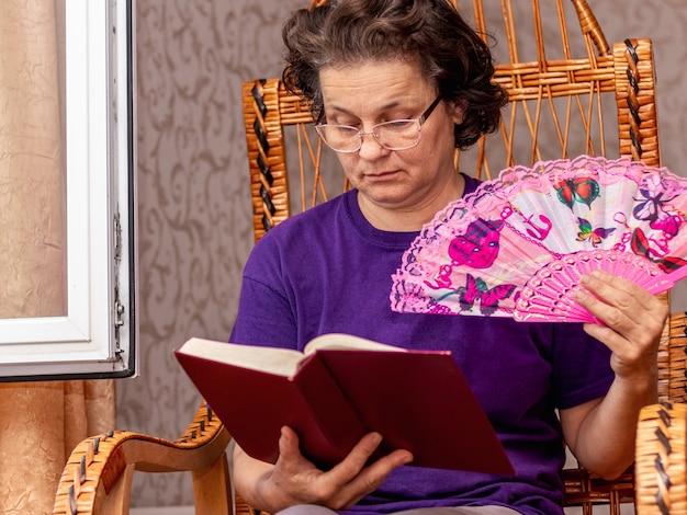 Een oudere vrouw met een waaier in haar hand leest de bijbel. vrouw in een stoel met een boek bij het open raam