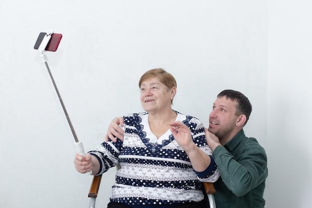 Een oudere vrouw met haar zoon praten aan de telefoon, de selfiestick in de hand